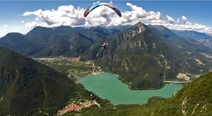 Parapendio in volo sulle acque del lago dei Tre Comuni in Friuli